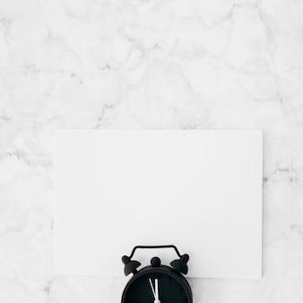 Despertador sobre el papel en blanco blanco sobre fondo de mármol con textura