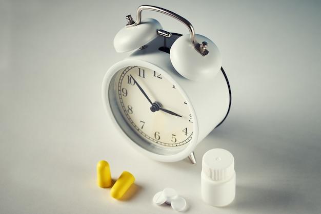 Despertador, tapones para los oídos y pastillas en blanco