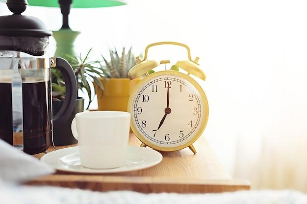 Despertador y taza de café en la cama en una habitación soleada. comienzo de la mañana fácil, comienzo de día positivo, despertar, concepto de nuevo día