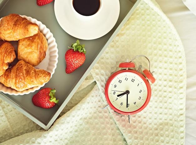 Despertador y taza de café en la cama en una habitación soleada. comienzo de la mañana fácil, comienzo positivo del día, despertar, nuevo día, desayuno en el concepto de cama. endecha plana, vista superior