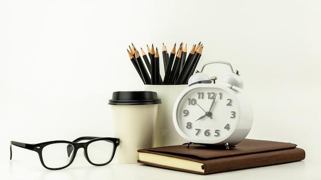 Despertador, taza de café de papel, lápiz y un cuaderno de cuero en el fondo de escritorio blanco con espacio de copia.