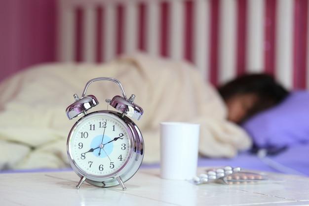 Despertador y vaso de agua, medicina con mujer durmiendo en la habitación