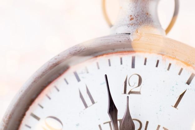 El despertador de la vendimia está mostrando la medianoche. son las doce en punto, navidad y bokeh, concepto festivo de vacaciones feliz año nuevo sobre fondo claro bokeh