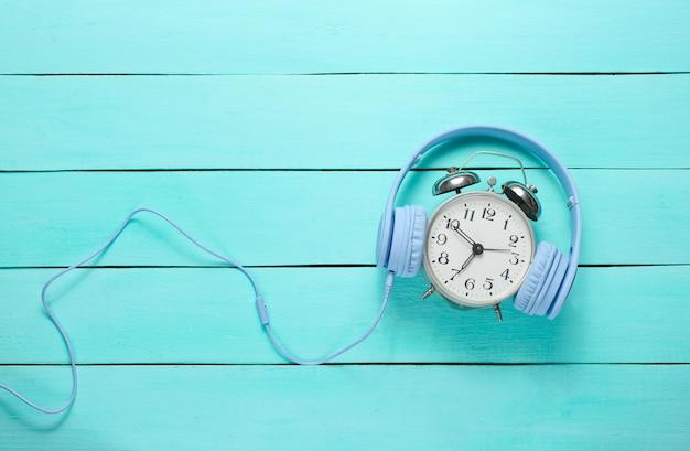Despertador vintage con auriculares sobre fondo de madera