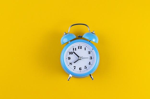 Despertador vintage azul sobre fondo de color amarillo