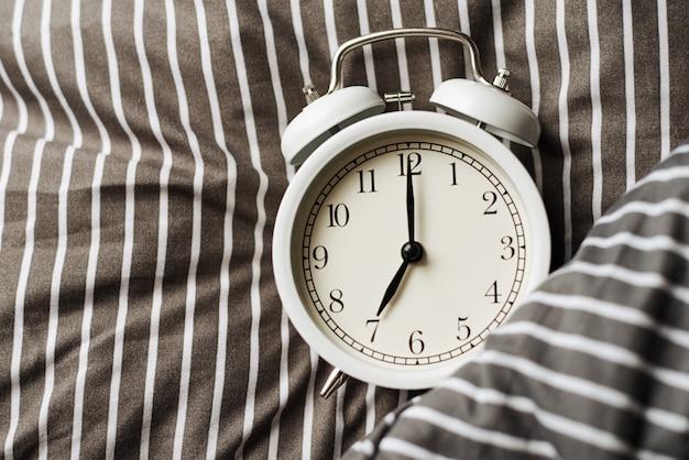 Despertador vintage blanco sobre almohada en la cama. wale up y concepto de mañana
