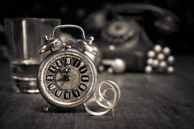 Despertador vintage que muestra cinco hasta la medianoche y un teléfono antiguo.