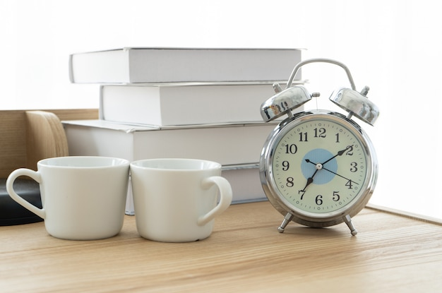 Despertador vintage con taza de café blanco.
