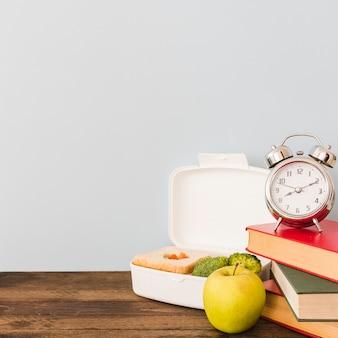 Despertador y libros cerca de comida saludable