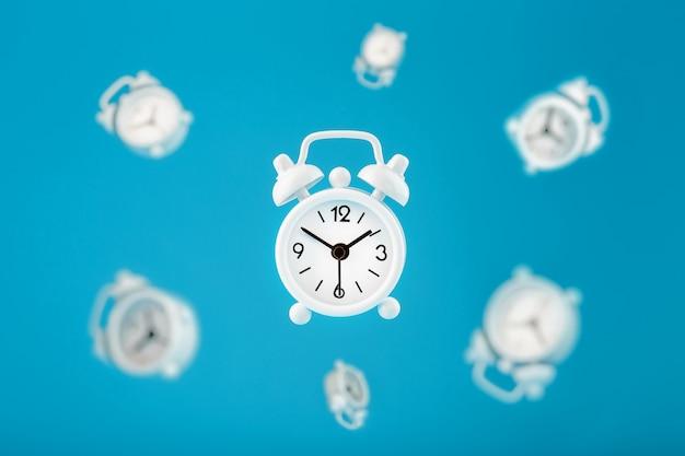 Despertadores retros blancos en vuelo en el centro, aislados en un fondo azul. concepto moderno creativo de la naturaleza muerta de tiempo de vuelo.