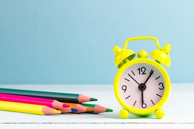 Despertarse temprano en la mañana a la escuela junto al despertador. vida escolar.