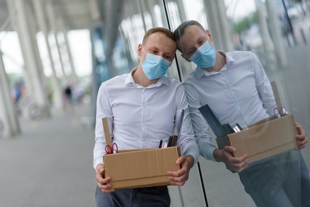 Despido de un empleado por epidemia de coronavirus. empleado despedido sper contra la pared de la oficina con sus suministros de oficina.