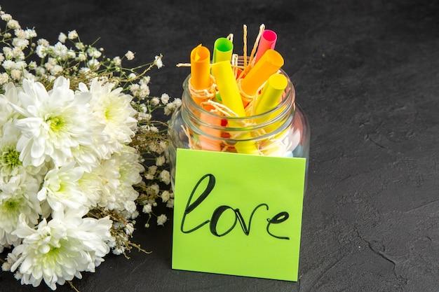 Desplazamiento de la vista inferior deseos de colores papeles en jar ramo de flores amor escrito en una nota adhesiva verde sobre fondo oscuro