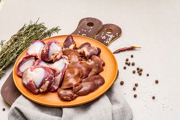 Despojos de pato crudo fresco: corazón, hígado, estómago. especias secas, sal, ají. tablas de cortar de madera,