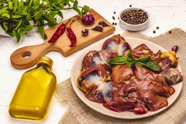 Despojos de pollo crudo fresco: corazón, hígado, estómago con especias secas, sal marina, ají, aceite de oliva, menta fresca sobre fondo de masilla blanca