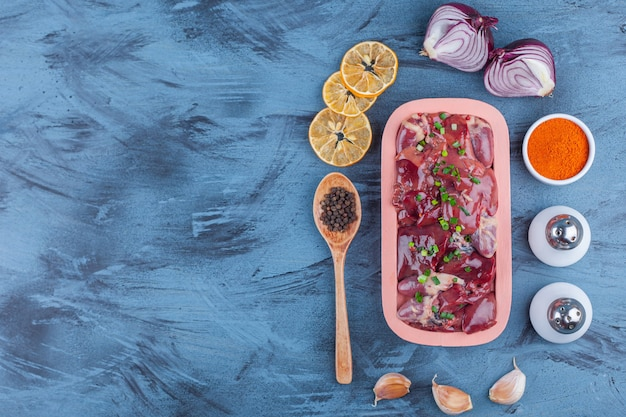 Despojos de pollo en un plato de madera, especias, sal, especias con ajo cuchara y limón seco, sobre fondo azul.