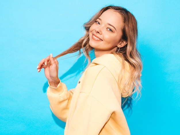 Despreocupada mujer posando junto a la pared azul en el estudio. modelo positivo divirtiéndose. toca su cabello