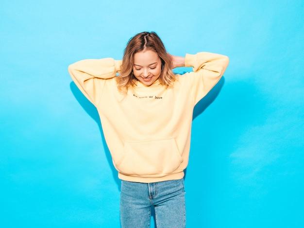 Despreocupada mujer posando junto a la pared azul en el estudio. modelo positivo divirtiéndose