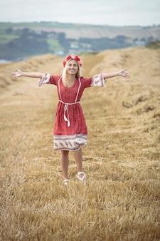Despreocupada mujer rubia de pie en el campo