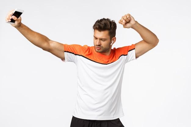Despreocupado, descarado, guapo, joven, atleta masculino en camiseta deportiva, levantando las manos y cerrar los ojos