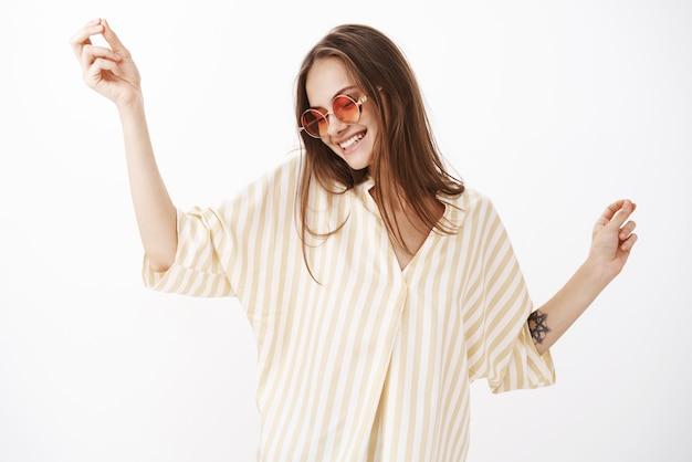 Despreocupado encantado y feliz joven mujer moderna con elegantes gafas de sol rojas y blusa de rayas amarillas bailando femenino y alegre sonriendo de alegría divirtiéndose