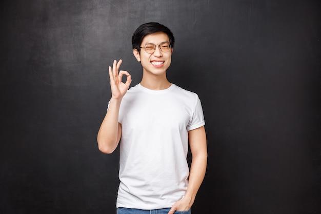 Despreocupado, feliz, sonriente, joven asiático se quedó satisfecho después de probar un nuevo producto, visitar la empresa y usar sus buenos servicios, mostrar un buen cartel y guiñar con alegría, contento sobre la pared negra