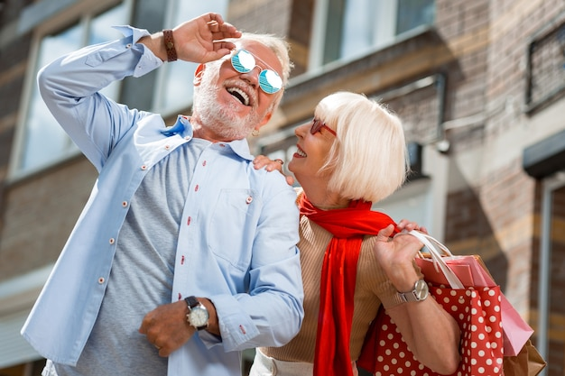 Después de las compras. cintura para arriba de la adorable pareja de ancianos con estilo disfrutando de un paseo juntos mientras sostienen paquetes con compras compradas recientemente