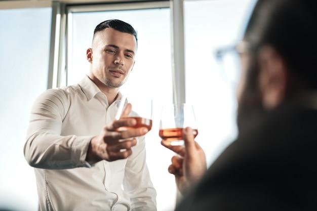 Después de la negociación. dos prósperos socios comerciales bebiendo coñac después de una negociación exitosa