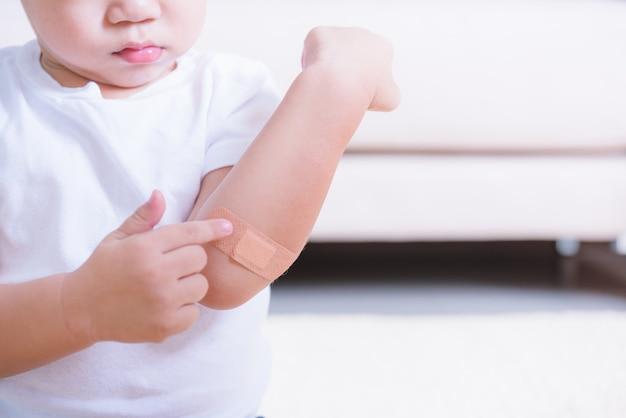 Después de que la madre aplique vendaje adhesivo de yeso en la herida del brazo del niño niño con copyspace