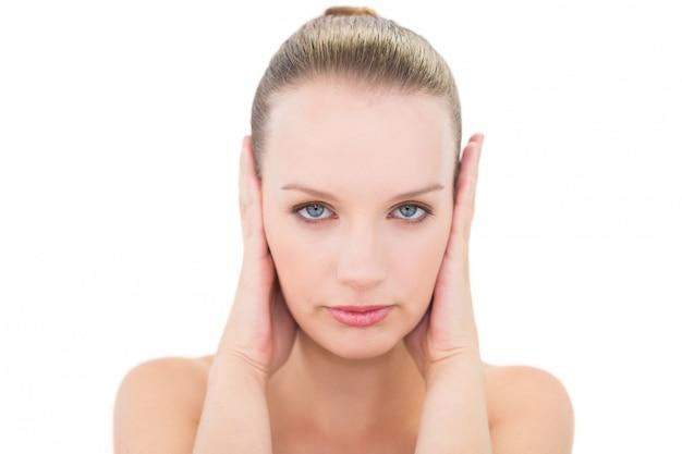 Destacada guapa modelo rubia que bloquea sus orejas.
