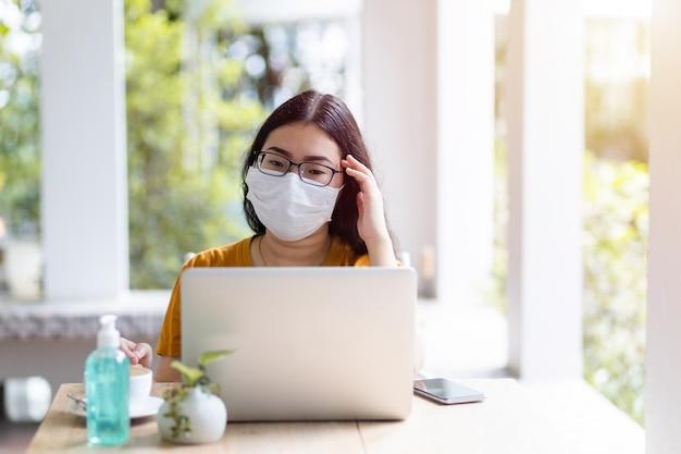 Destacado de la gente independiente mujer de negocios con máscara protectora casual que tiene un dolor de cabeza después de las pérdidas comerciales trabajando con una computadora portátil