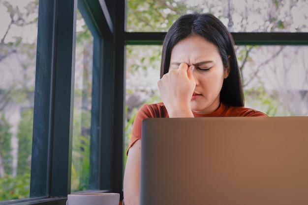 Destacó empresaria dolor de cabeza trabajando en la computadora portátil. emoción humana negativa sentimientos de expresión facial