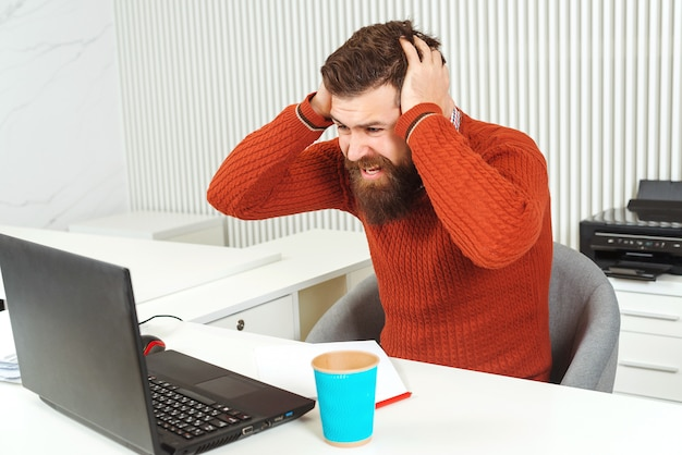 Destacó el hombre barbudo sosteniendo la cabeza con la mano en el lugar de trabajo. hombre mirando portátil. el gerente tiene problemas, malas noticias. broker e indicadores financieros. la caída de los precios de las acciones.