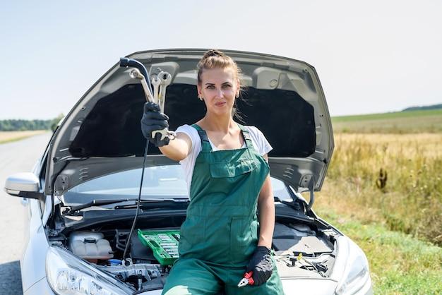 Destacó la mujer joven mirando el motor de su coche. problemas de viaje por carretera. el coche necesita una reparación.