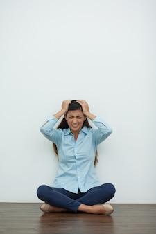 Destacó la mujer se sienta en suelo y clutching cabeza