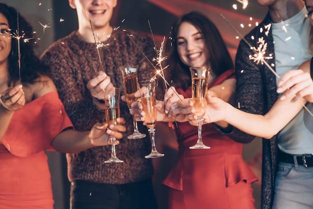 Destellos por todas partes. amigos multirraciales celebran año nuevo y sostienen luces de bengala y vasos con bebida