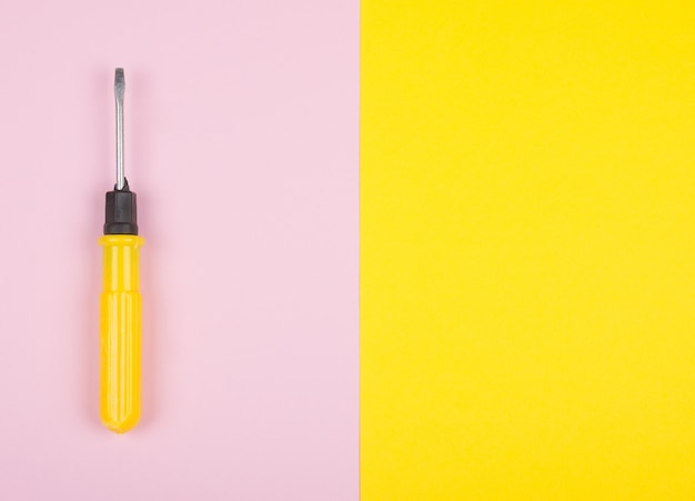Destornillador amarillo sobre un fondo rosa y amarillo dividido