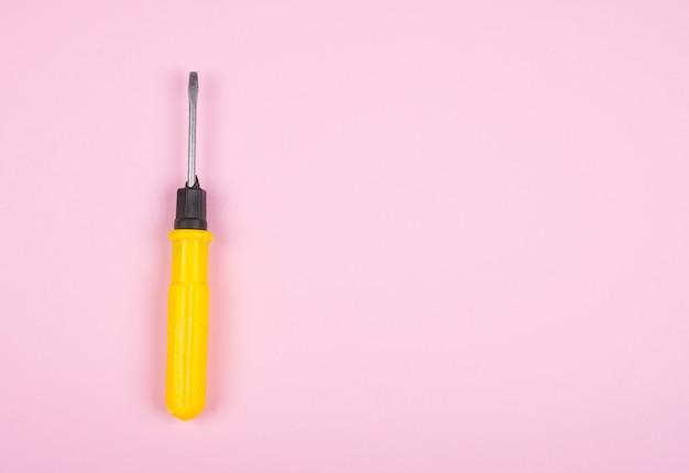 Destornillador amarillo sobre un fondo rosa pastel