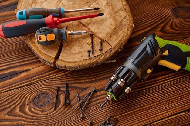 Destornilladores y tornillos autorroscantes en tocón, primer plano, mesa de madera. instrumento profesional, equipo de carpintero, herramientas de carpintería.