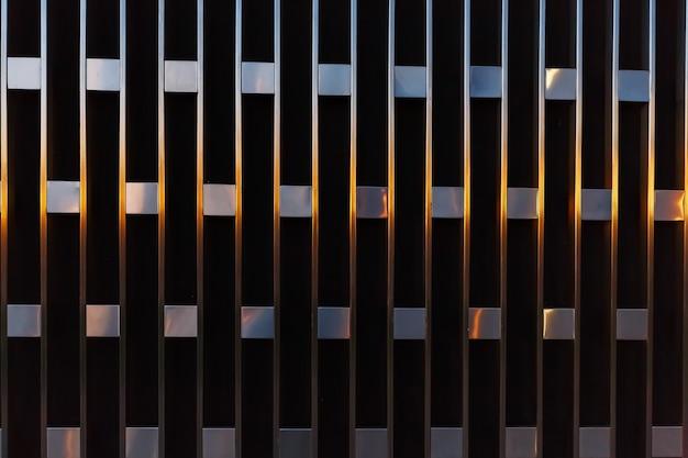 Detalle arquitectónico abstracto de líneas verticales con cuadrados de metal al atardecer.