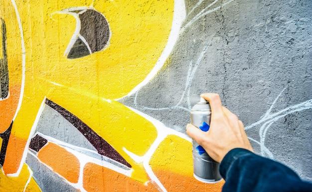 Detalle del artista callejero pintando coloridos graffiti en la pared pública