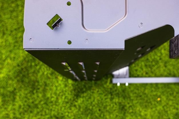 Detalle de una barbacoa metálica durante su montaje, para hacer parrillas al aire libre.