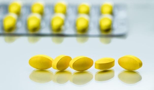 Detalle de disparo macro de píldoras de tableta ovalada amarilla sobre fondo blanco con blister como fondo