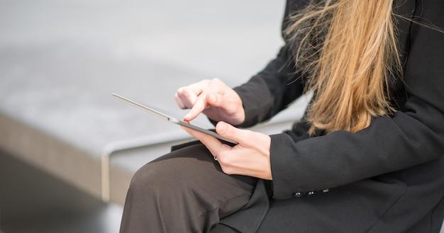 Detalle de una empresaria usando su tableta mientras está sentado en un banco en una ciudad