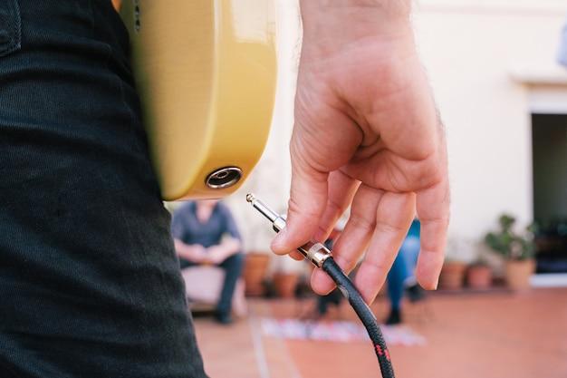 Detalle del enchufe en el instrumento musical antes de un concierto íntimo. cerca de una mano masculina desconectando un cable de música a una guitarra eléctrica. industria del ocio, el tiempo libre, el entretenimiento y la música.