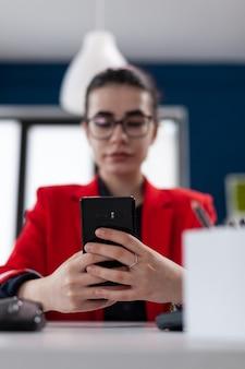 Detalle de enfoque selectivo en el teléfono inteligente mientras la empresaria está enviando mensajes de texto