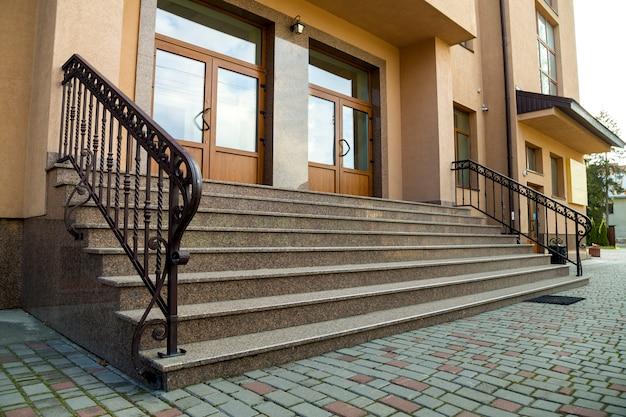 Detalle de la fachada de una casa. nuevas escaleras de granito con barandas metálicas.