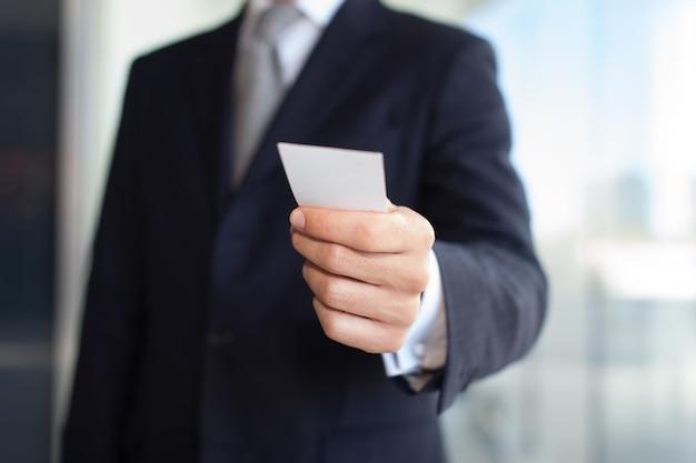 Detalle de un hombre de negocios dando una tarjeta de visita