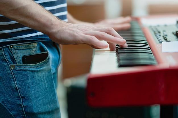 Detalle del jugador del teclado de un grupo pop durante un espectáculo