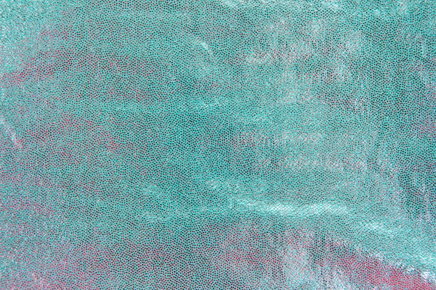 Detalle de lentejuelas turquesas en fondo.